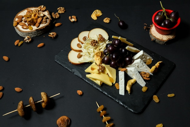 Top view cheese plate with grapes and nuts on a stand with dried fruits on a black table