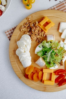 Top view of cheese plate with nuts on a table