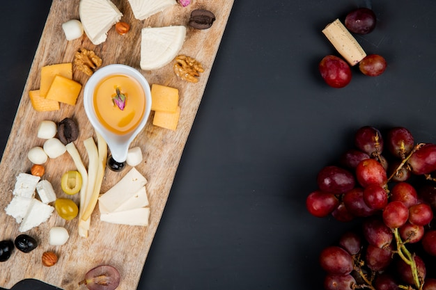 Top view of cheese set with cheddar brie string feta and butter olive nuts on cutting board with grape and cork on black