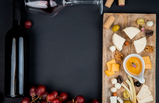 Top view of cheese set with cheddar brie string feta and butter olive walnuts on cutting board with bottle and glass of red wine and corks on black with copy space