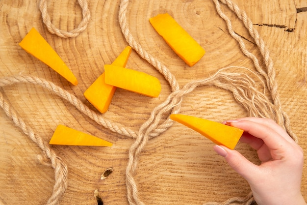 Top view cheese slices rope cheese in female hand on wooden table