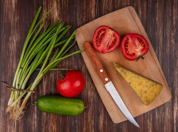 Vista dall'alto fette di formaggio con pomodori e coltello su un supporto con cetriolo e cipolle verdi su fondo in legno
