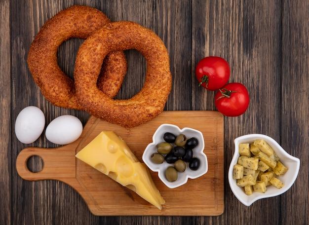 Vista dall'alto di formaggio con olive su una ciotola su una tavola di cucina in legno con uova e pomodori isolati su uno sfondo di legno
