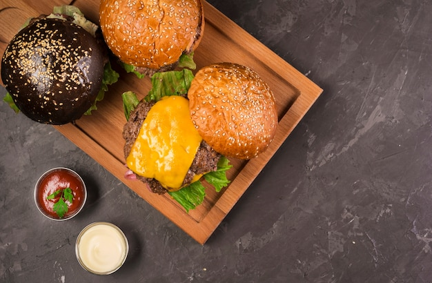 Top view cheeseburgers on a wooden board