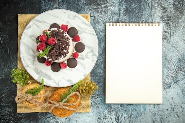 Чизкейк с шоколадом и малиной на белой овальной тарелке, перевязанный печеньем, на газете, рождественские украшения, блокнот на серой поверхности, вид сверху