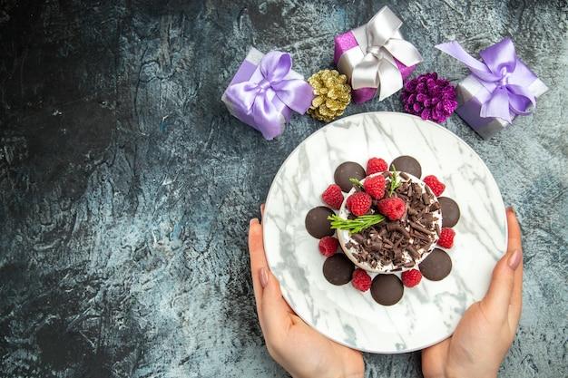灰色の表面の自由な場所で女性の手のクリスマスプレゼントの楕円形のプレートにチョコレートとトップビューのチーズケーキ