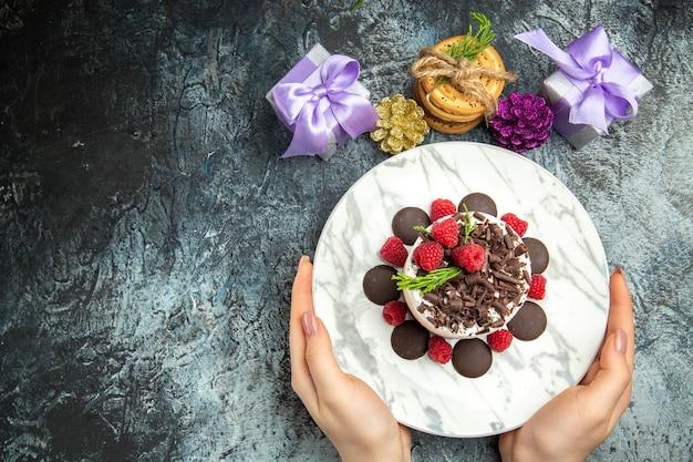 灰色の表面の空き領域に女性の手のクリスマスプレゼントの楕円形のプレートにチョコレートとトップビューのチーズケーキ