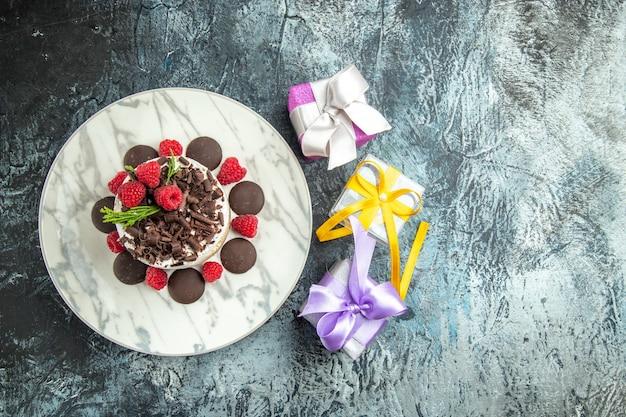 灰色の表面の空き領域に楕円形のプレートのクリスマスプレゼントにチョコレートとトップビューのチーズケーキ