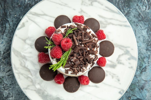 灰色の表面の白い楕円形のプレートにチョコレートとチーズケーキの上面図食品写真