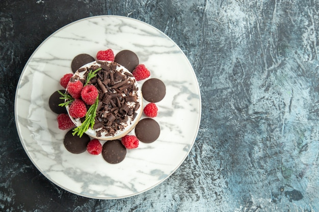 Top view cheesecake with chocolate on white oval plate on grey surface with free space