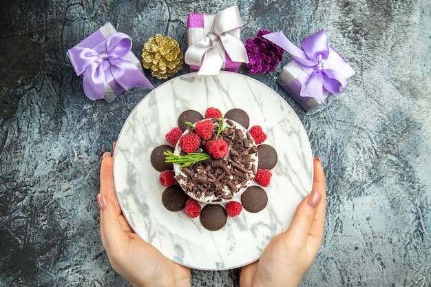 灰色の表面の空き領域に女性の手のクリスマスプレゼントの楕円形のプレートにラズベリーとチョコレートとトップビューチーズケーキ