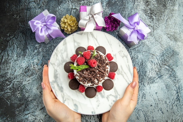 Vista dall'alto cheesecake al cioccolato con lamponi sul piatto ovale in donna mani regali di natale su uno spazio libero superficie grigia
