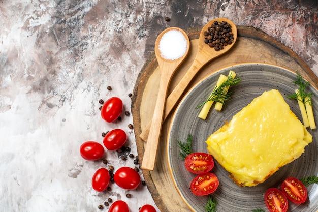 平面図安っぽいガーリックブレッドトマトプレート上の木のスプーン素朴なサービングボード上のチェリートマトテーブル上の
