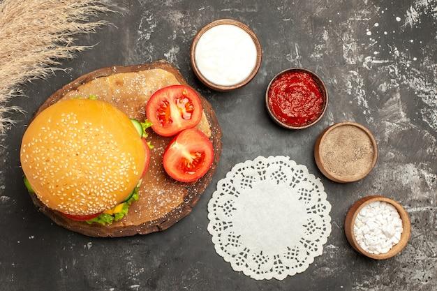 Vista dall'alto hamburger di carne di formaggio con condimenti sulle patatine fritte di carne panino panino scuro scrivania