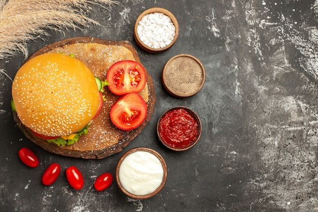 Top view cheesy meat burger with seasonings on a dark surface bun sandwich fast-food