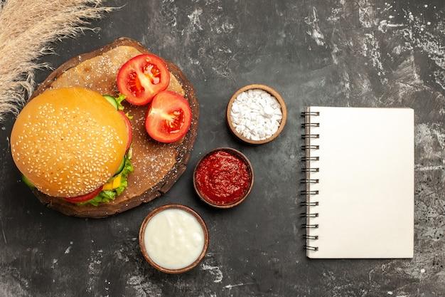 Vista dall'alto hamburger di carne di formaggio con condimenti sulle patatine fritte panino panino di carne superficie scura