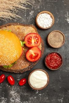 ダークフロアのパンサンドイッチファーストフードに調味料を入れたトップビューの安っぽいミートバーガー