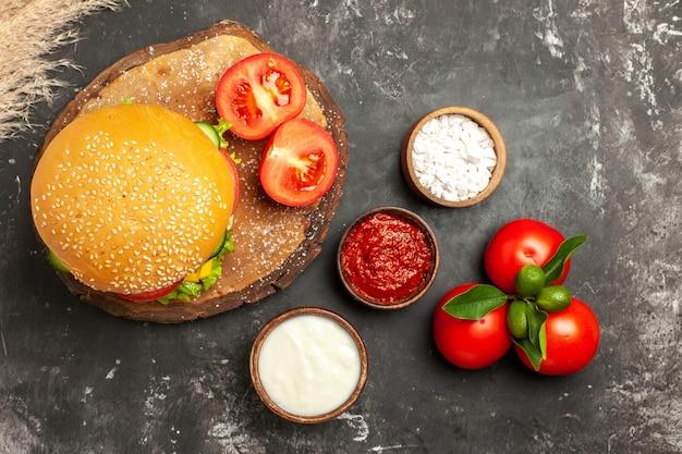 暗い表面のパンフライドポテトサンドイッチに調味料を入れた上面図の安っぽいミートバーガー
