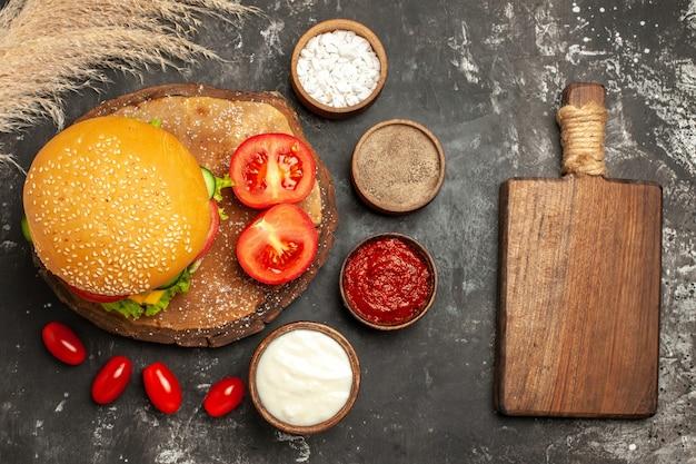 暗い表面のパンサンドイッチファーストフードに調味料を入れたトップビューの安っぽいミートバーガー