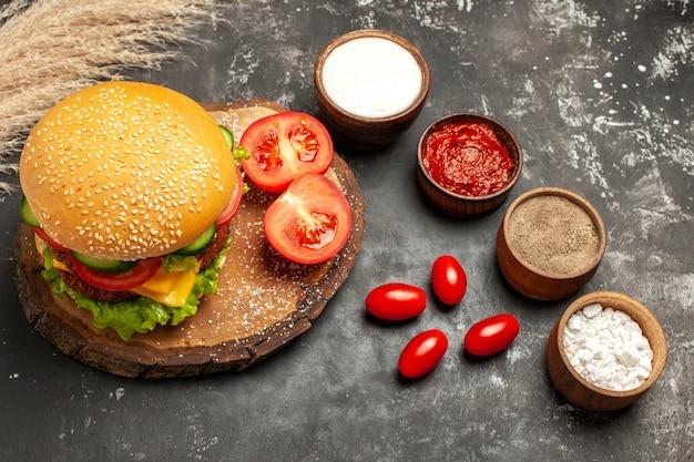 暗い床のパンサンドイッチミートフライに調味料を入れたトップビューの安っぽいミートバーガー