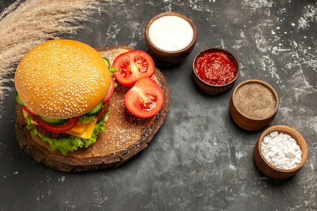 暗い表面のパンサンドイッチミートフライに調味料を入れたトップビューの安っぽいミートバーガー