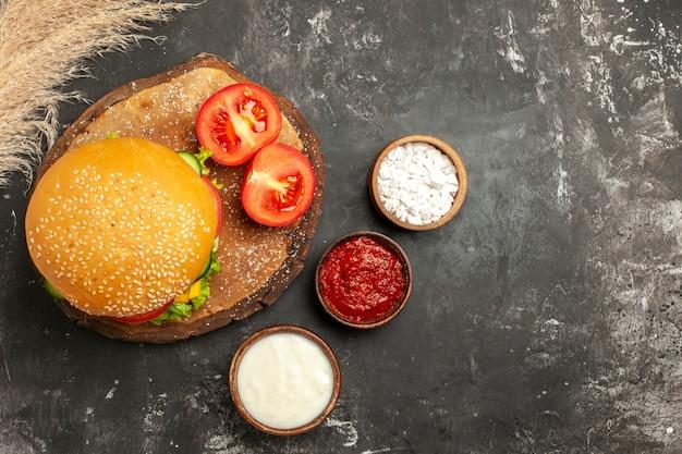 暗い表面の肉まんサンドイッチフライに調味料を入れた上面図の安っぽい肉バーガー