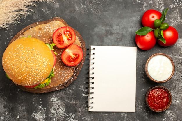 Vista dall'alto hamburger di carne di formaggio con pomodori sulla superficie scura panino patatine fritte di carne sandwich
