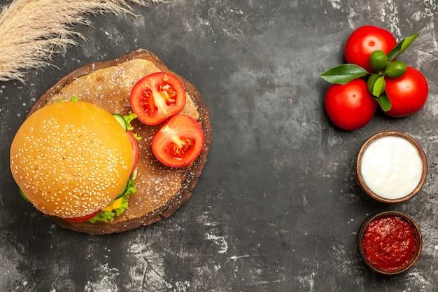 暗い床のパンフライドポテトサンドイッチにトマトとチーズのチーズバーガーの上面図