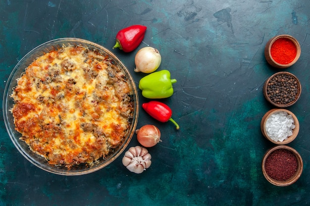 Вид сверху сырной мясной еды со свежими овощами и приправами на темно-синем столе еда мясная еда блюдо ужин в духовке