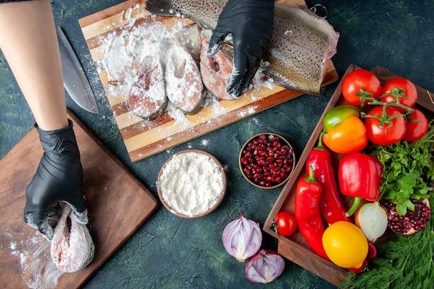 キッチンテーブルの木製ボード小麦粉ボウルに小麦粉の新鮮な野菜で魚のスライスをカバーする上面図のシェフ