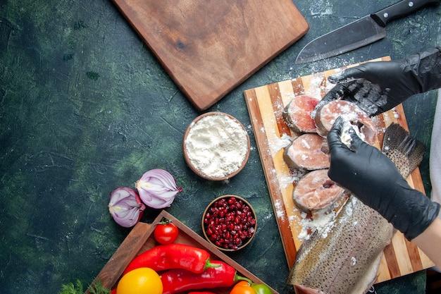 生の魚のスライスを木の板に小麦粉の新鮮な野菜で覆う上面図シェフキッチンテーブルの空きスペースに小麦粉ボウルナイフ