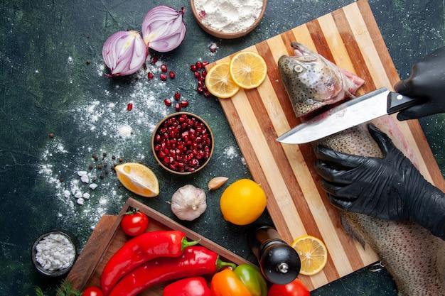 Вид сверху шеф-повар, режущий голову рыбы на разделочной доске, мельница для перца, миска для муки, семена граната в миске на кухонном столе