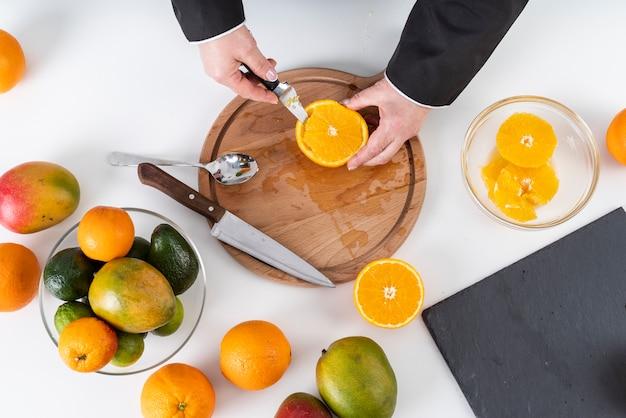 Vista superiore del cuoco unico che taglia un'arancia