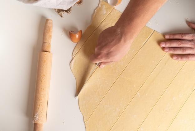 Вид сверху шеф-повара, формирующего пасту в полоску