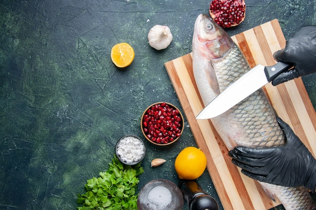 Top view chef with black gloves cutting raw fish on cutting board pepper grinder pomegranate seeds in bowl on kitchen table copy place