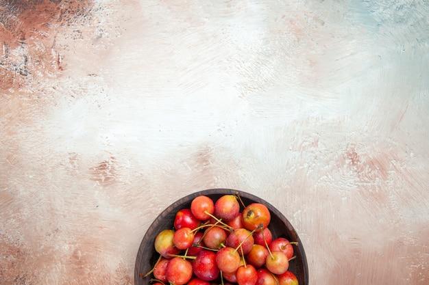 Vista dall'alto della ciotola di ciliegie delle appetitose ciliegie giallo-rosse sul tavolo