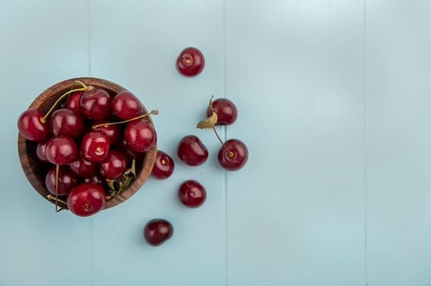 Top view of cherries in bowl and on blue background with copy space