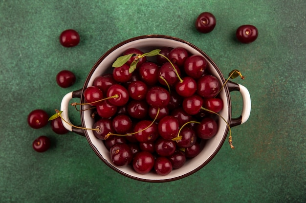 Top view of cherries in bowl and on green background