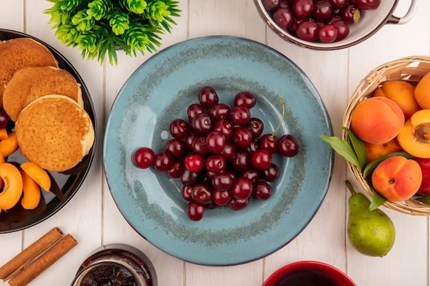Vista dall'alto di ciliegie in piastra e frittelle fette di albicocca nella piastra con cesto di albicocche e marmellata di pera cannella su sfondo di legno