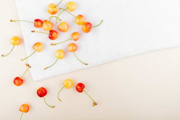 Top view of cherries on white cloth and white surface with copy space