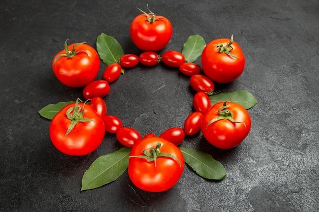 여유 공간이있는 어두운 땅에 상위 뷰 체리와 빨간 토마토 베이 잎