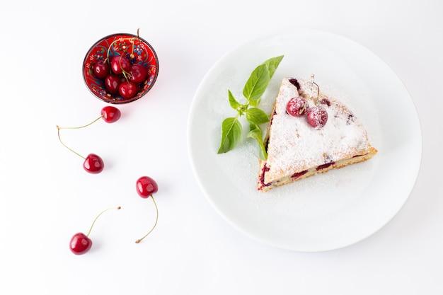 トップビューチェリーケーキスライスホワイトプレートの内側で美味しくておいしい、白いデスクケーキビスケットの甘い焼きたてのチェリー