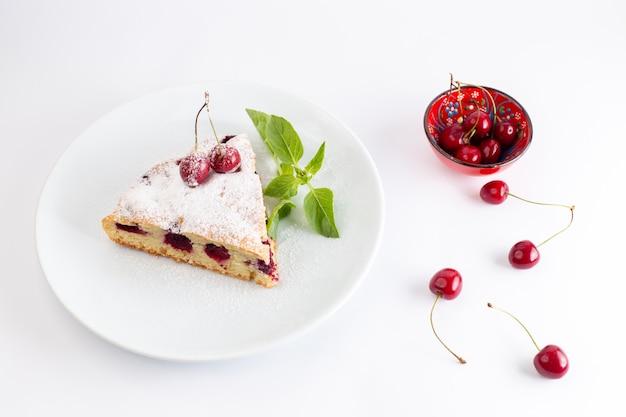 トップビューチェリーケーキスライスホワイトプレートの内側のおいしいとおいしい白い背景のケーキビスケット砂糖生地を焼く