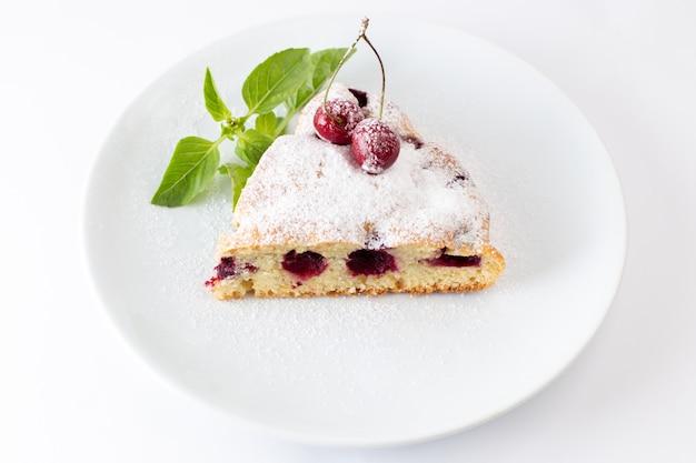 Вид сверху кусочек вишневого торта вкусный и вкусный внутри белой тарелки на белом фоне торт бисквитное сладкое тесто выпечка
