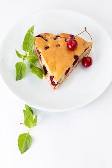 白い背景の上のケーキのビスケットの甘い生地を焼く白いプレート内のトップビューチェリーケーキスライス