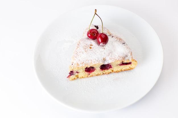 白い背景の上に砂糖粉と白いプレート内のトップビューチェリーケーキスライス甘い砂糖生地を焼く