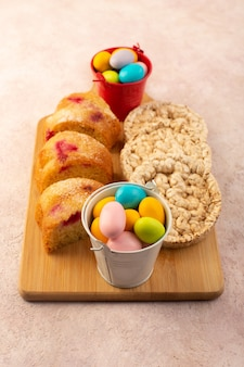 A top view cherry cake slices with candies and biscuits on the bright-pink desk cake biscuit sugar sweet