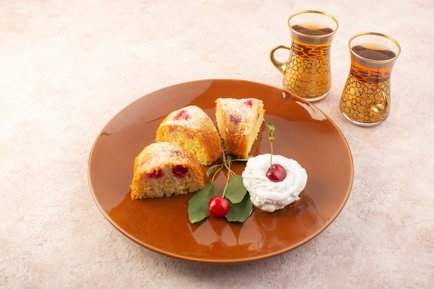 A top view cherry cake slices with cream inside round plate on the pink desk cake biscuit sugar sweet