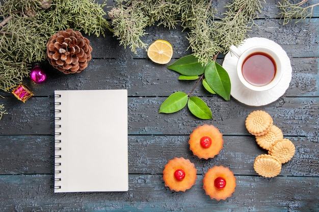 Vista dall'alto cupcakes ciliegia rami di abete foglie fetta di limone una tazza di biscotti da tè e un taccuino sul tavolo di legno scuro