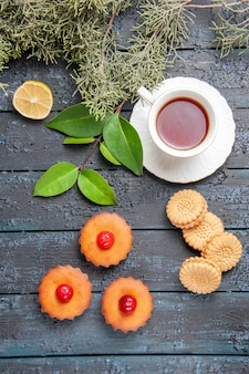 Top view cherry cupcakes fir-tree branches slice of lemon a cup of tea biscuits and leaves on dark wooden ground